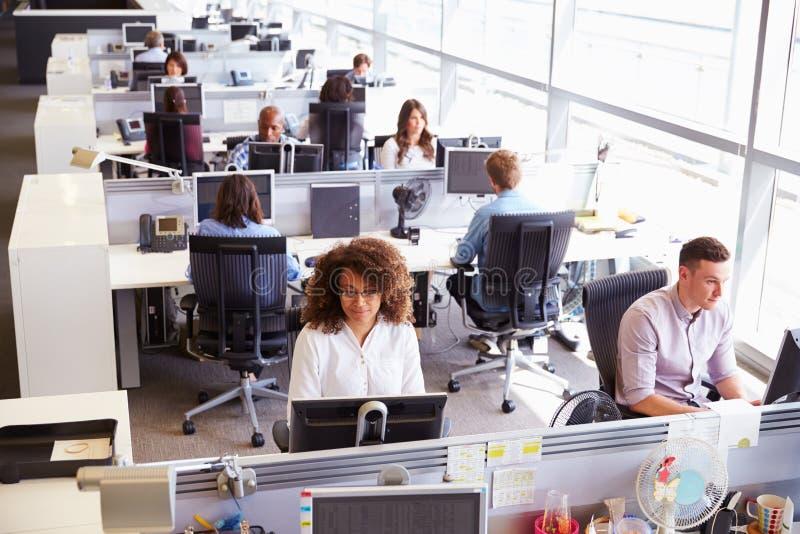 Trabalhadores ocasionalmente vestidos em um escritório de plano aberto ocupado imagens de stock
