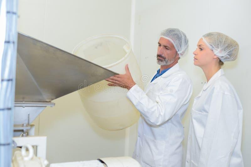 Trabalhadores que adicionam o material na fábrica imagens de stock royalty free