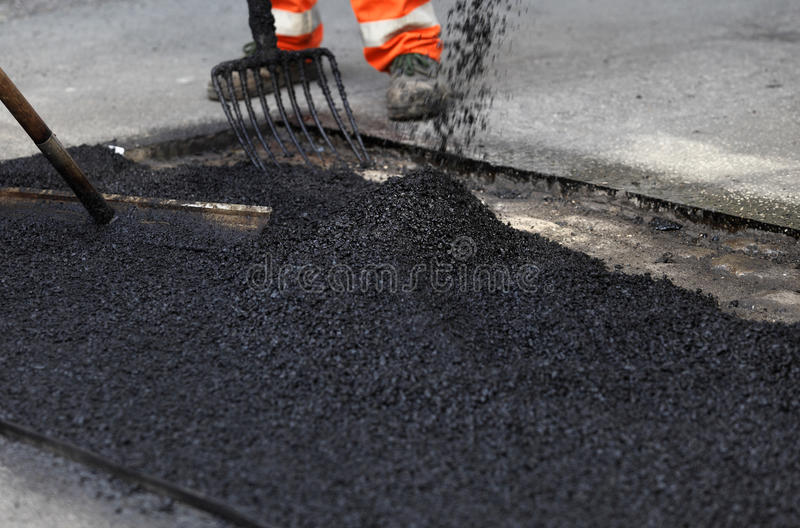 Trabalhadores que alisam o asfalto foto de stock