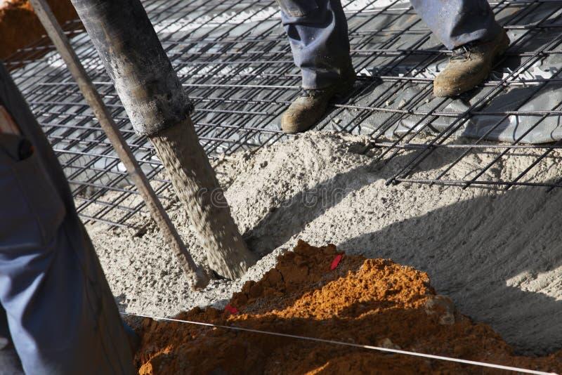Trabalhadores que derramam o cimento para fundações imagens de stock