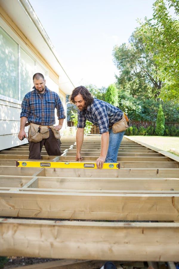 Trabalhadores que examinam ao nível da madeira no local imagens de stock royalty free