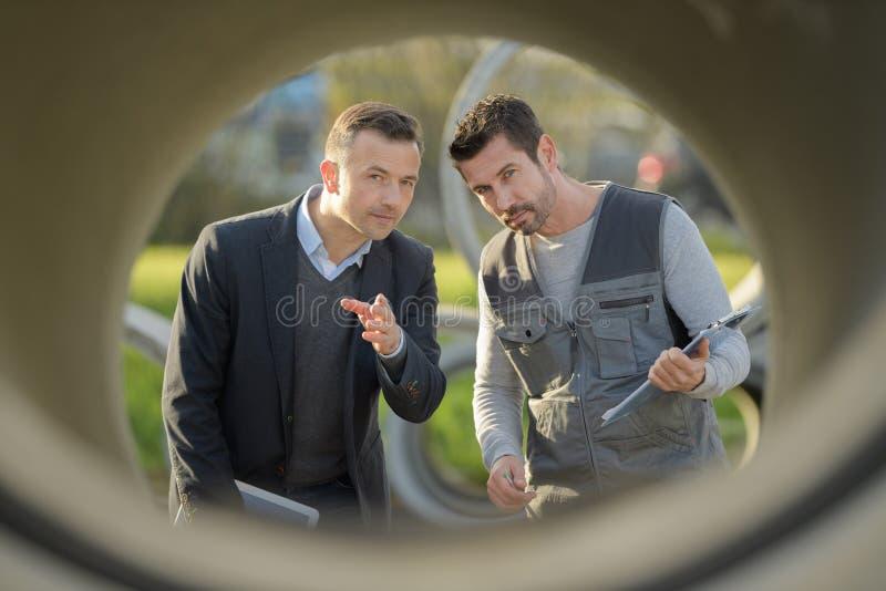 Trabalhadores que falam através da tubulação do concreto pré-fabricado fotos de stock