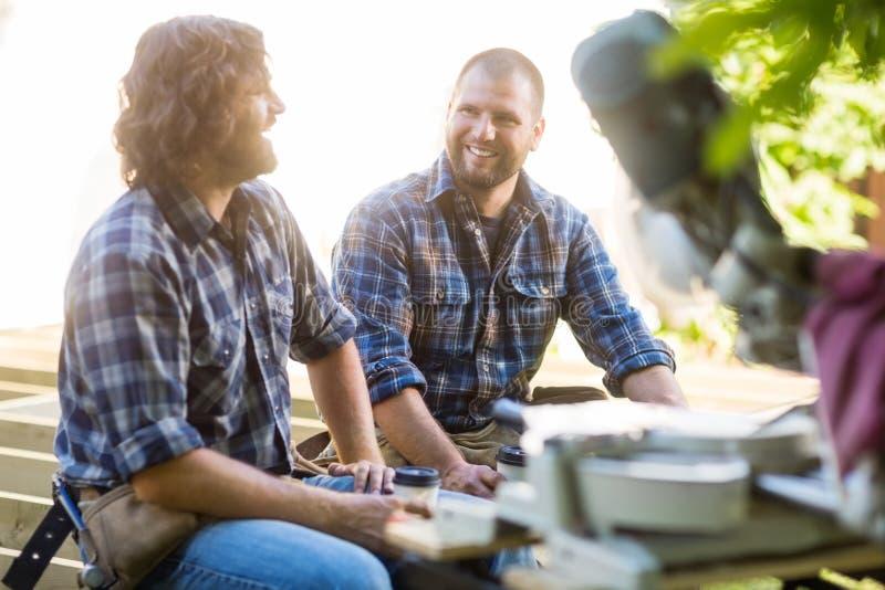Trabalhadores que guardam copos de café descartáveis quando foto de stock royalty free