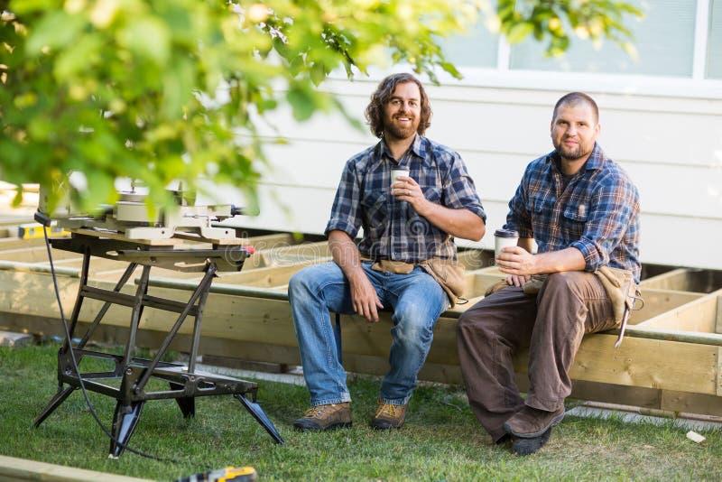 Trabalhadores que guardam copos descartáveis ao sentar-se sobre imagens de stock