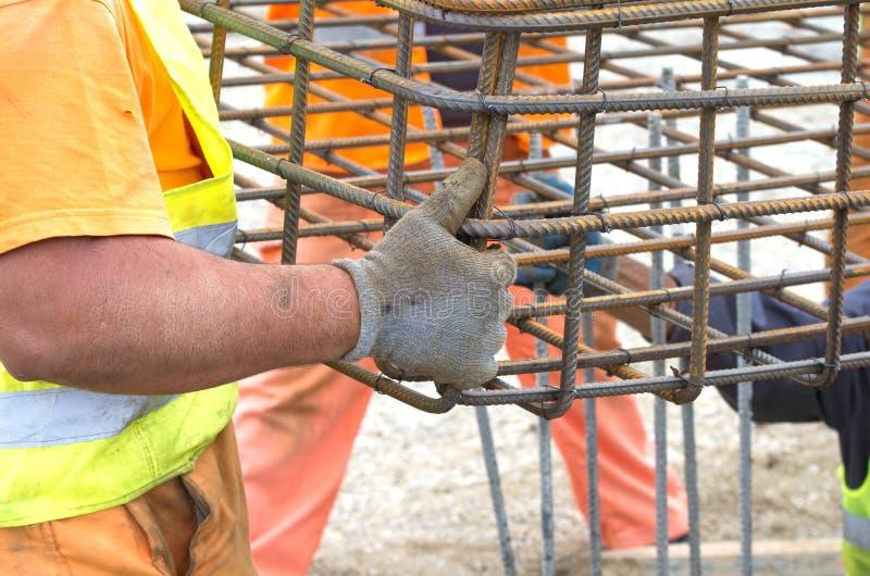 Trabalhadores que instalam a estrutura do reforço imagens de stock