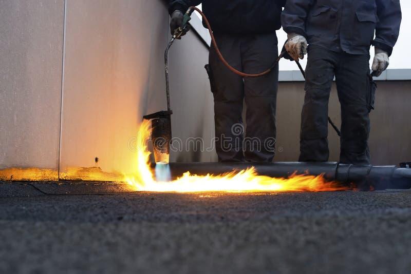 Trabalhadores que instalam a telhadura sentida com calor imagens de stock royalty free