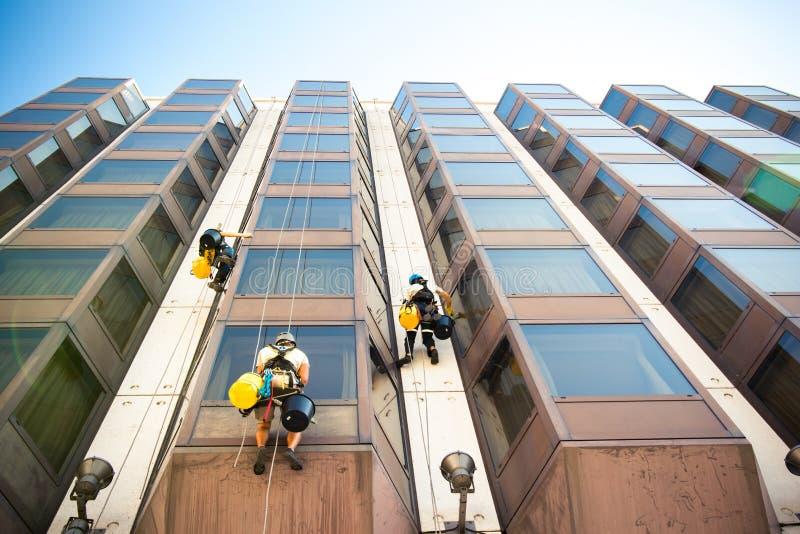 Trabalhadores que limpam as janelas na construção de vidro foto de stock