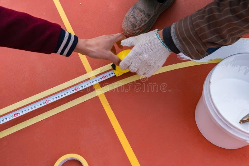 Trabalhadores que medem e que marcam a atividade secundárioa no assoalho para o estádio exterior fotografia de stock