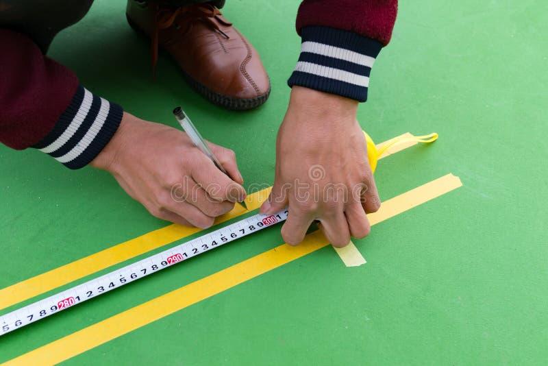 Trabalhadores que medem e que marcam a atividade secundárioa no assoalho para o estádio exterior fotos de stock royalty free