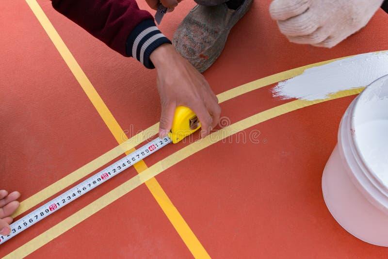 Trabalhadores que medem e que pintam a atividade secundárioa no assoalho imagens de stock