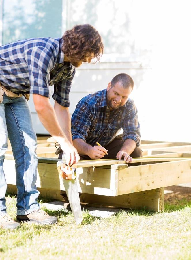 Trabalhadores que medem a madeira no canteiro de obras imagem de stock royalty free