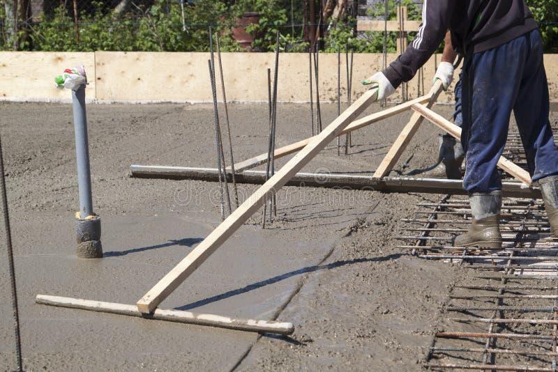 trabalhadores que nivelam a laje de cimento fresca com uma ferramenta de funcionamento de madeira especial fotografia de stock