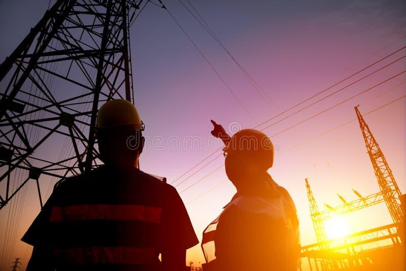 trabalhadores que olham a torre e a subestação de poder com por do sol b imagens de stock royalty free
