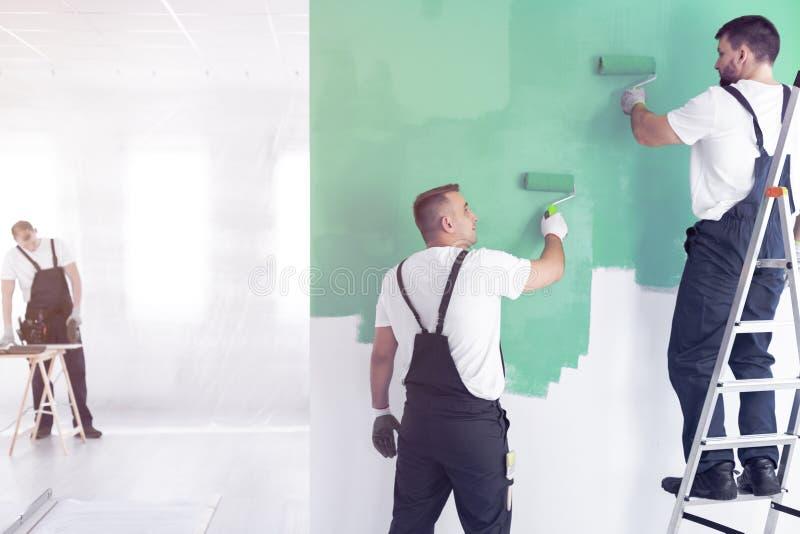 Trabalhadores que pintam um verde e uma posição da parede em uma escada quando aleta fotos de stock royalty free
