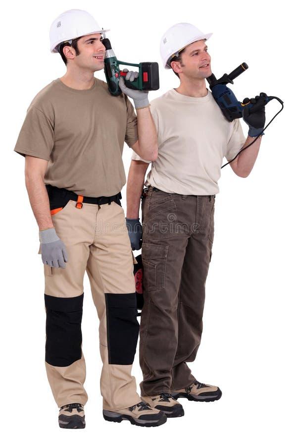 Trabalhadores que prendem brocas imagem de stock