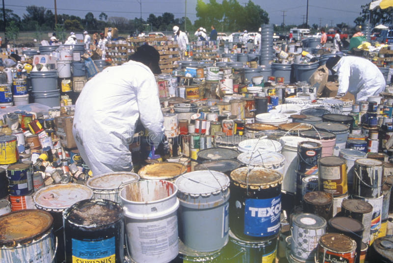 Trabalhadores que seguram desperdícios tóxicos do agregado familiar no local waste da limpeza no Dia da Terra na planta de Unocal foto de stock royalty free