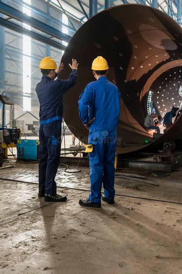 Trabalhadores que supervisionam a fabricação de um cilindro metálico imagem de stock royalty free