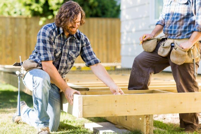 Trabalhadores que trabalham no quadro de madeira na construção foto de stock royalty free
