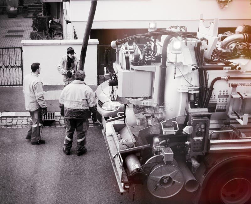 Trabalhadores que usam o caminhão do esgoto imagens de stock