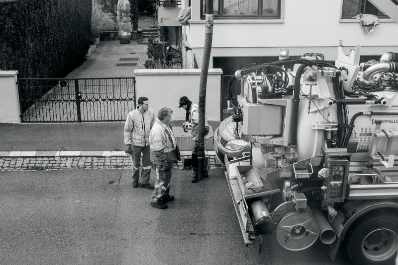 Trabalhadores que usam o caminhão do esgoto e a grande tubulação que trabalham no clogg fotografia de stock