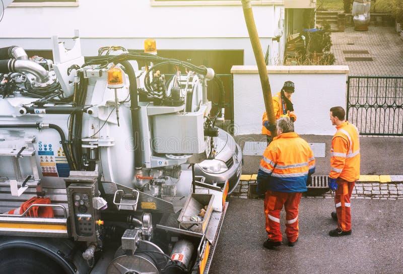 Trabalhadores que usam o caminhão do esgoto e a grande tubulação que trabalham no clogg imagem de stock royalty free