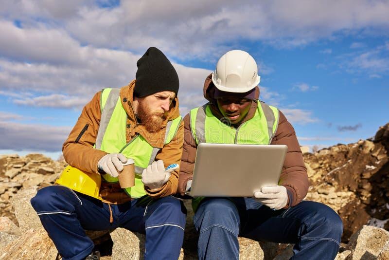 Trabalhadores que usam o portátil no local da escavação foto de stock