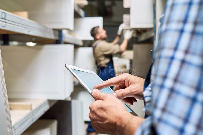 Trabalhadores que usam a tabuleta digital no armazém imagens de stock