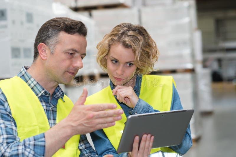 Trabalhadores que usam a tabuleta digital no armazém fotos de stock