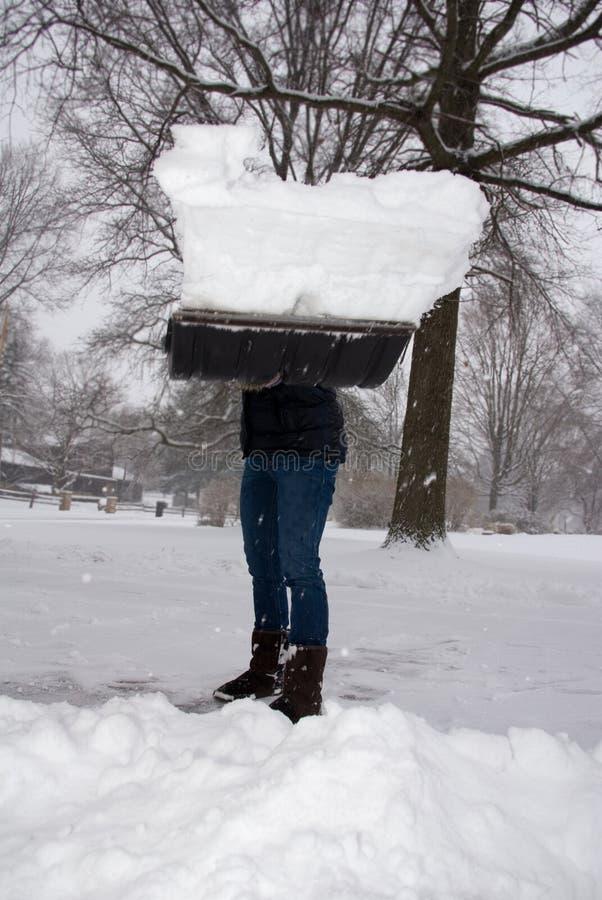 Trabalhando com pá a carga máxima da neve jogada no visor imagem de stock royalty free