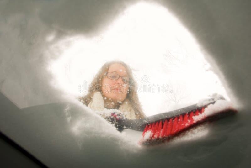 Trabalhando com pá a opinião de raspagem do para-brisa da neve do interior do carro fotos de stock