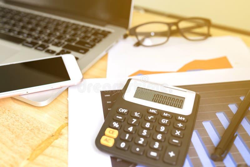 Trabalhando em notebooks desktop com calculadora para fazer negócios, laptop em mesa de investimento em carteira de madeira foto de stock