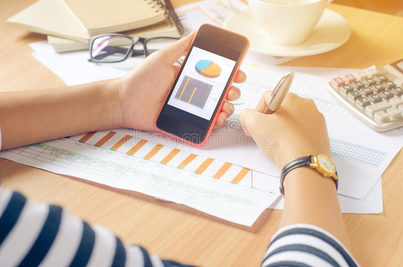 Trabalhando em uma mesa numérica na análise móvel, contabilidade financeira Representando graficamente o Internet, fotos de stock