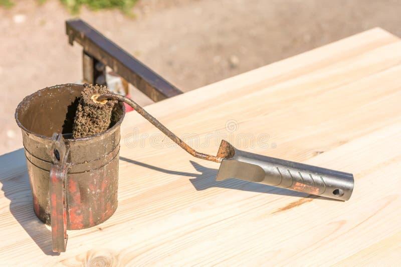 Trabalhando uma placa de madeira com o esmalte de madeira da preservação com um rolo de pintura e uma cubeta da pintura imagem de stock