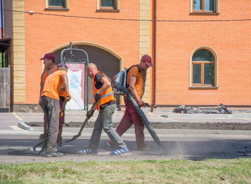 Trabalhe a brigada usando ferramentas para espalhar a migalha do asfalto nos furos na estrada Um trabalhador que funde para fora  imagens de stock
