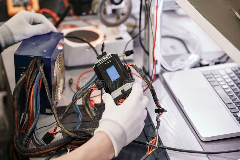 Trabalhe com a fonte de alimentação do ` s do computador Dispositivo da microeletrônica Mãos do close-up de um trabalhador do ser imagens de stock
