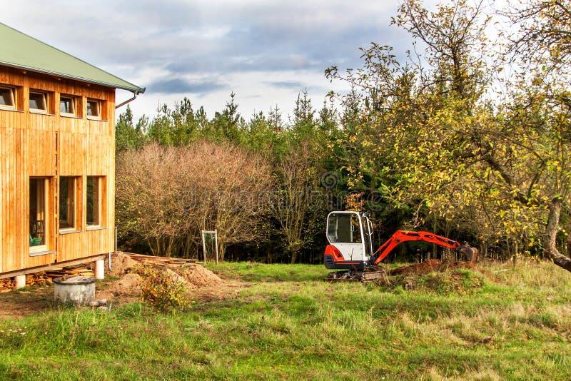 Trabalhe no canteiro de obras de uma casa ecológica A máquina escavadora ajusta o terreno Um escavador pequeno no jardim imagem de stock