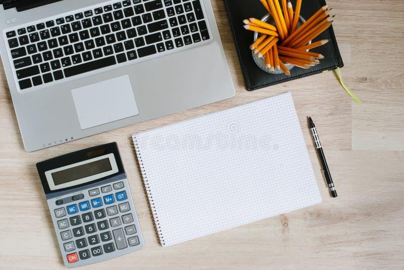 Trabalhe a tabela da mesa de escritório com portátil, marque-a, fontes e calculadora Vista superior com espaço da cópia fotografia de stock royalty free