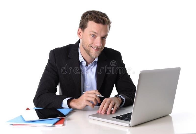 Trabalho atrativo novo do homem de negócios feliz na mesa do computador satisfeita e sorriso relaxado imagens de stock royalty free