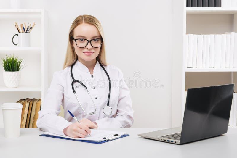 Trabalho bonito novo da mulher do doutor feliz e sorriso no hospital, sentando-se na tabela imagens de stock