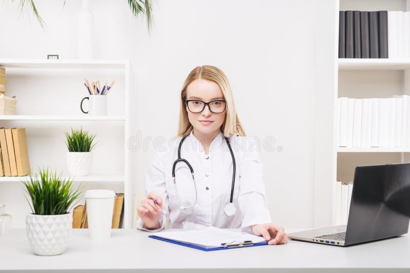 Trabalho bonito novo da mulher do doutor feliz e sorriso no hospital, sentando-se na tabela fotografia de stock royalty free