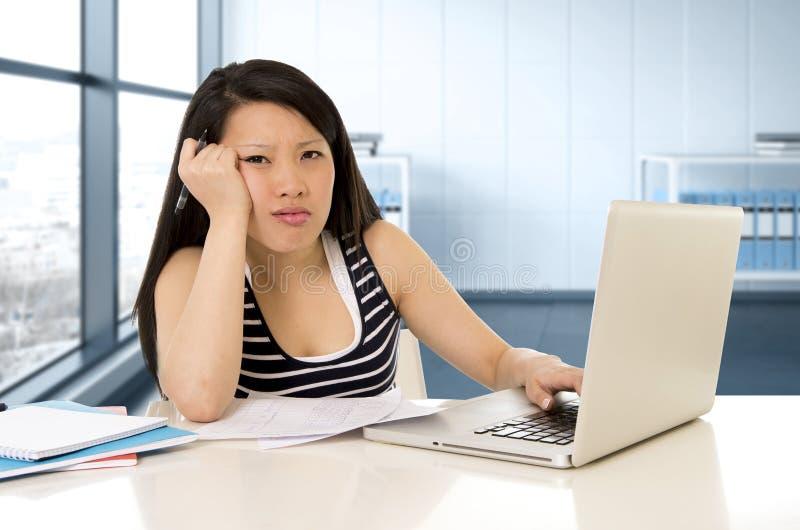 Trabalho cansado asiático chinês do estudante ou da mulher de negócio e estudo no portátil do computador fotos de stock royalty free