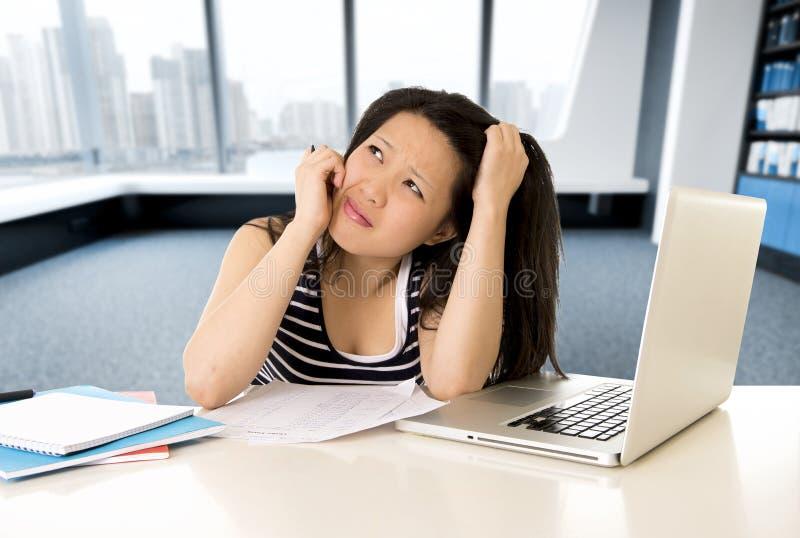 Trabalho cansado asiático chinês do estudante ou da mulher de negócio e estudo no portátil do computador fotos de stock
