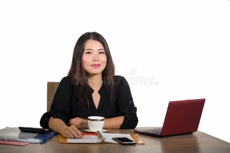 Trabalho chinês asiático bem sucedido bonito e feliz novo da mulher de negócio relaxado no levantamento seguro de sorriso da mesa fotografia de stock royalty free