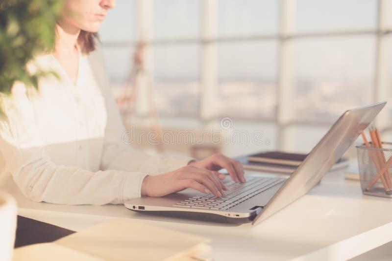 Trabalho com a mulher do portátil que escreve um blogue Mãos fêmeas no teclado fotos de stock royalty free