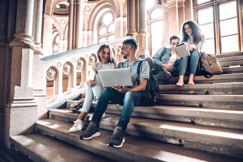 Trabalho com os povos que o motivam e inspiram Grupo de estudantes que estudam ao sentar-se em escadas na universidade imagem de stock