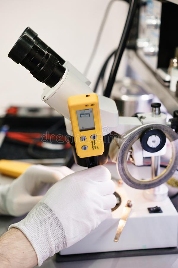Trabalho com um microscópio Dispositivo da microeletrônica Mãos do close-up de um trabalhador do serviço que repara o smartphone  foto de stock royalty free