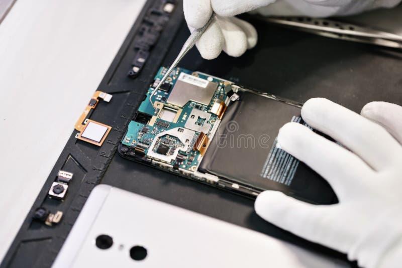 Trabalho com um microscópio Dispositivo da microeletrônica Mãos do close-up de um trabalhador do serviço que repara o smartphone  imagem de stock royalty free