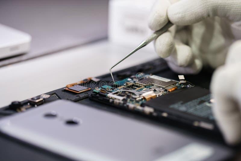 Trabalho com um microscópio Dispositivo da microeletrônica Mãos do close-up de um trabalhador do serviço que repara o smartphone  fotos de stock