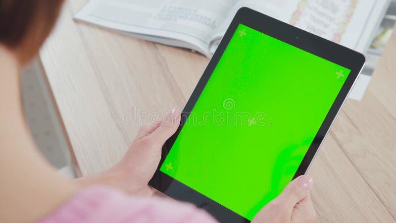 Trabalho com um tablet pc: tela verde e uma tabuleta nas mãos foto de stock