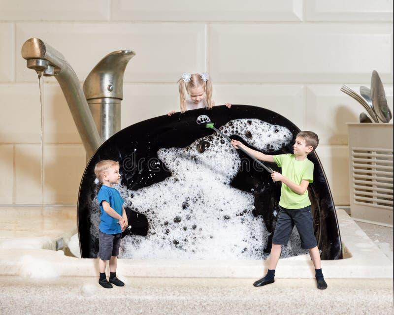 Trabalho criativo: três crianças em miniatura lavam uma grande placa preta com espuma Conceito de trabalho doméstico foto de stock